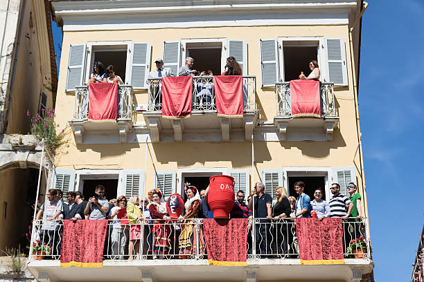 corfians throw clay pots from  balconies on holy saturday, corfu. - greek easter stock photos and pictures