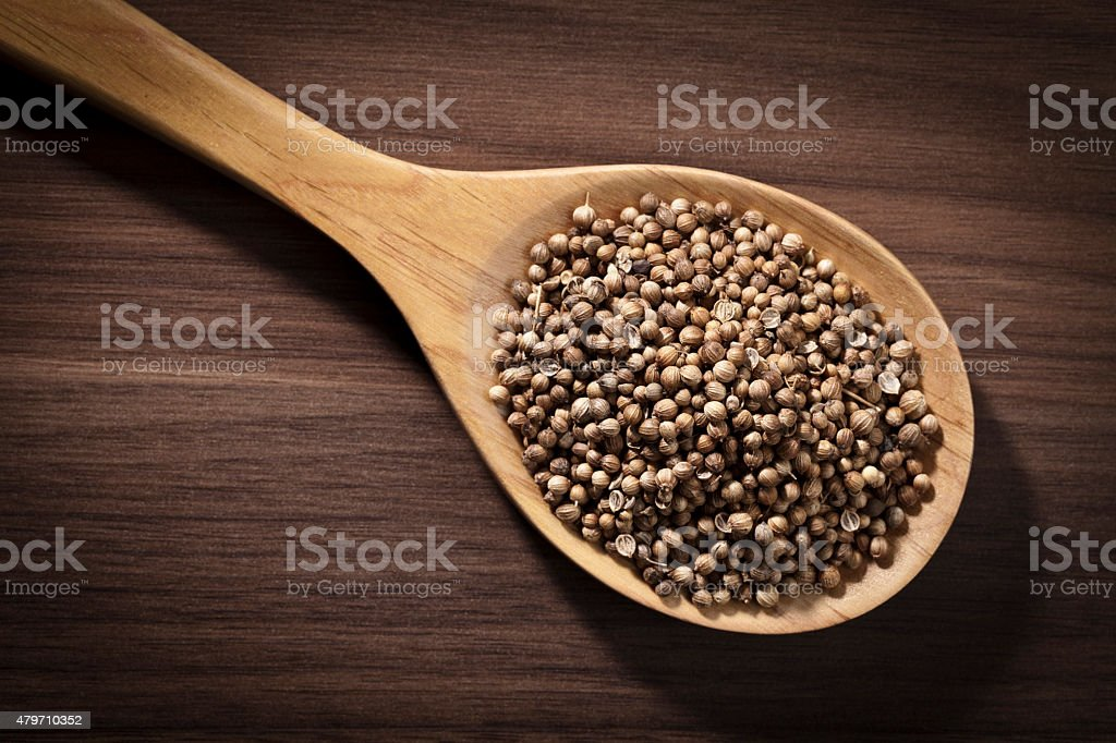 Coriander seeds in a wooden spoon shot directly above stock photo