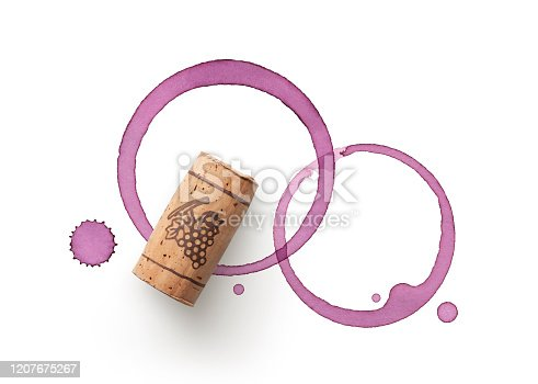 Cork and red wine stains on white background.