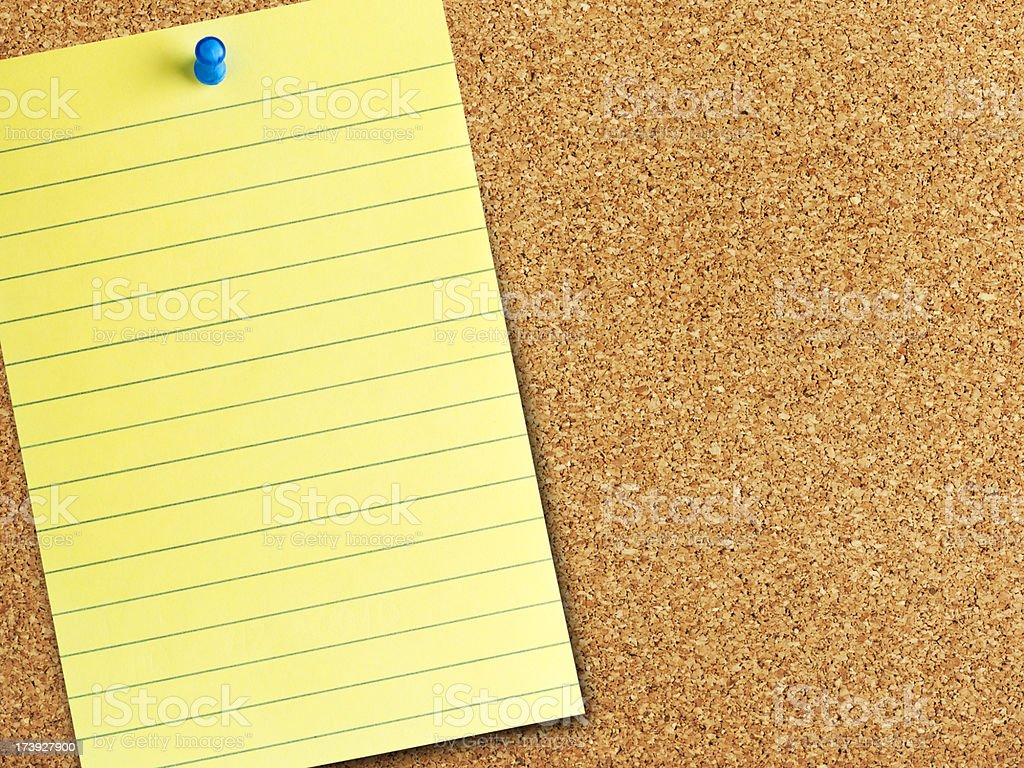Cork background with a yellow post it note royalty-free stock photo
