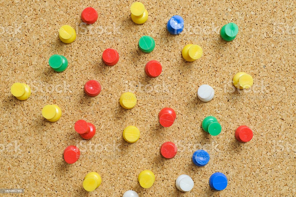 Cork board with red yellow green and white drawing pins royalty-free stock photo