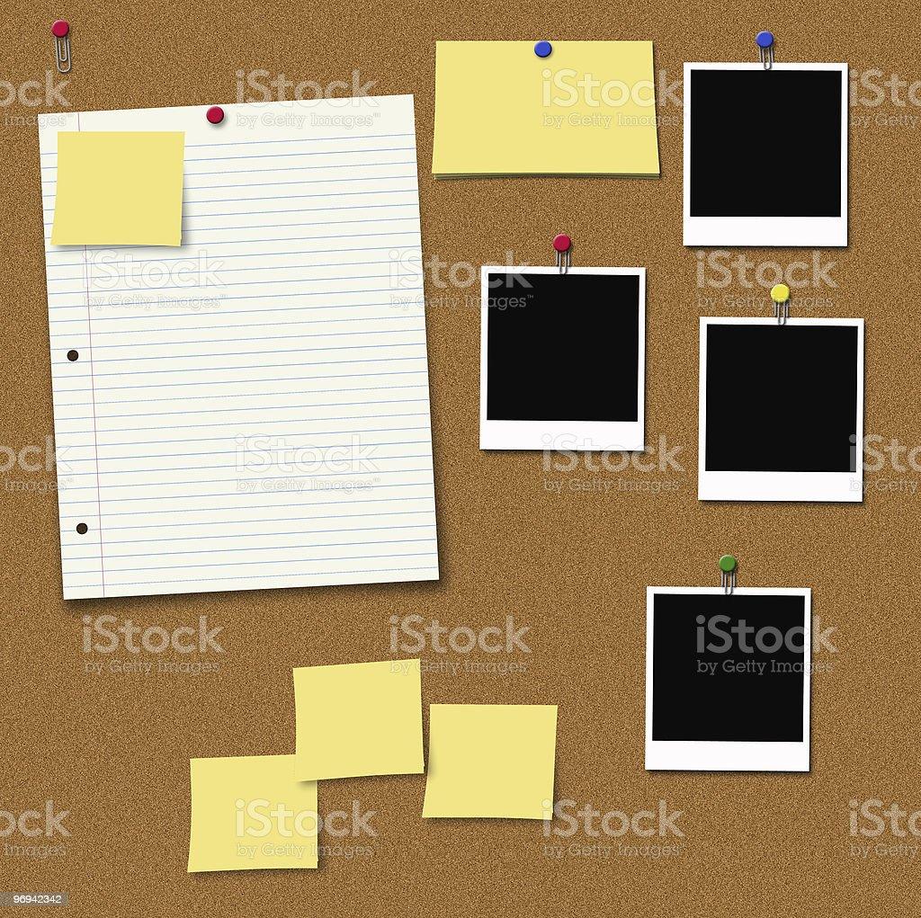 Cork thumbtack board with paper, tacks, and Polaroids royalty-free stock photo
