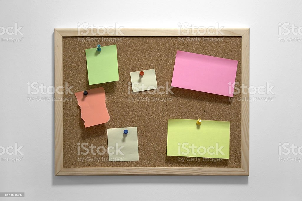 Corkboard with colorful Post-It notes and pins royalty-free stock photo