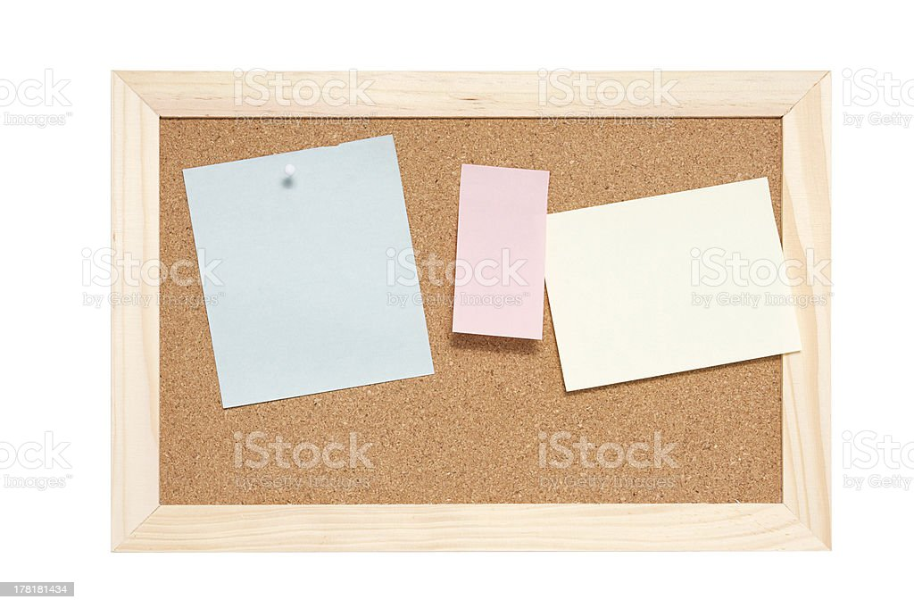 Corkboard with empty blue pink and yellow notes stock photo
