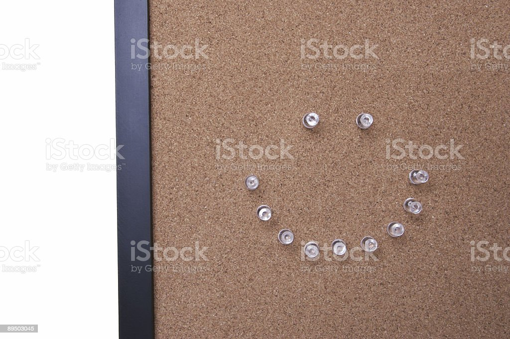 Corkboard with pins in the shape of a smiley face royaltyfri bildbanksbilder