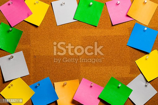 Corkboard/Bulletin Board bordered completely by very disorderly multicolored sticky type square notes.  The notes are all blank and easily edited with copy and the center of the image is completely open for copywriting.