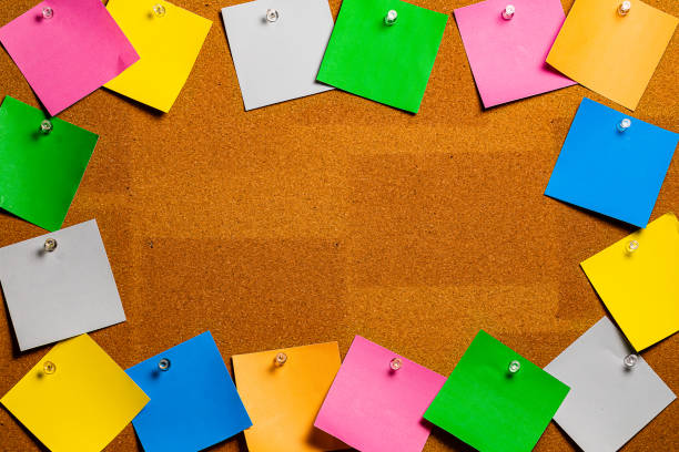 corkboard/bulletin board bordered completely by very disorderly multicolored sticky type square notes.  the notes are all blank and easily edited with copy and the center of the image is completely open for copywriting. - bulletin board stock pictures, royalty-free photos & images