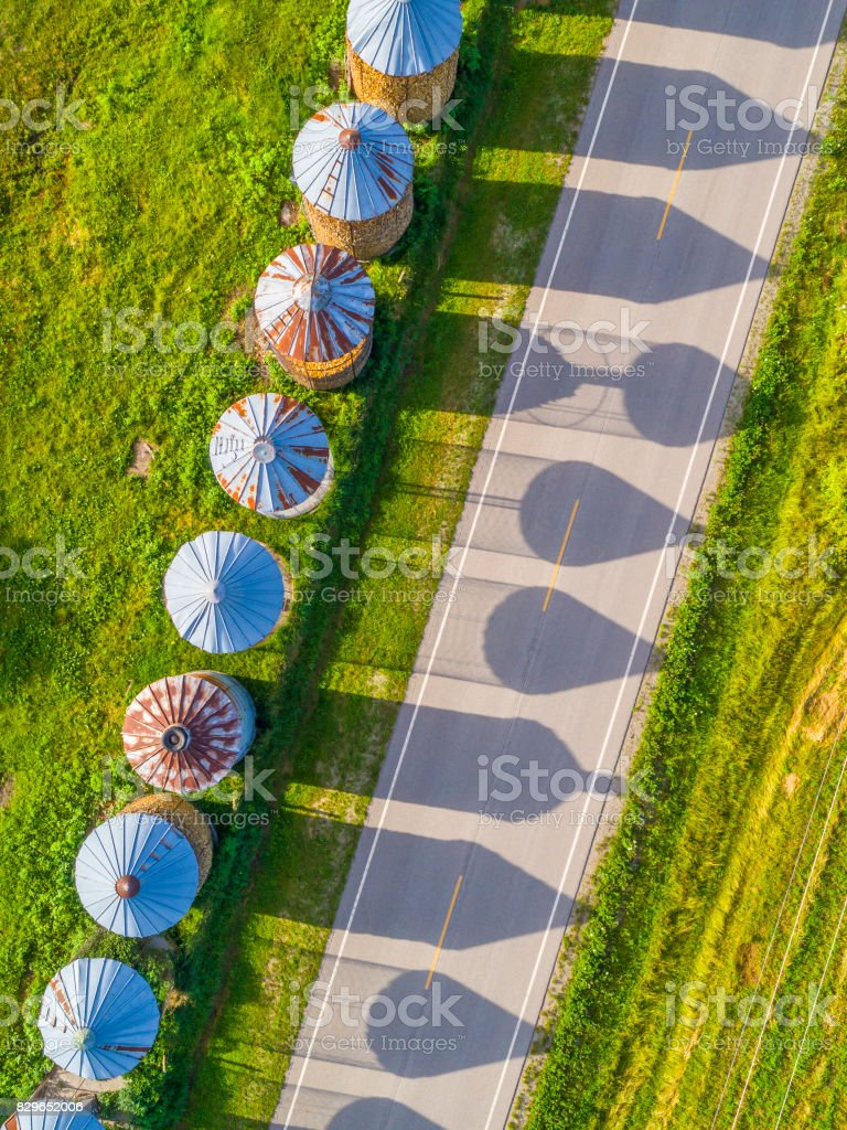 Corn cribs cast long shadows on country road, aerial view. stock photo