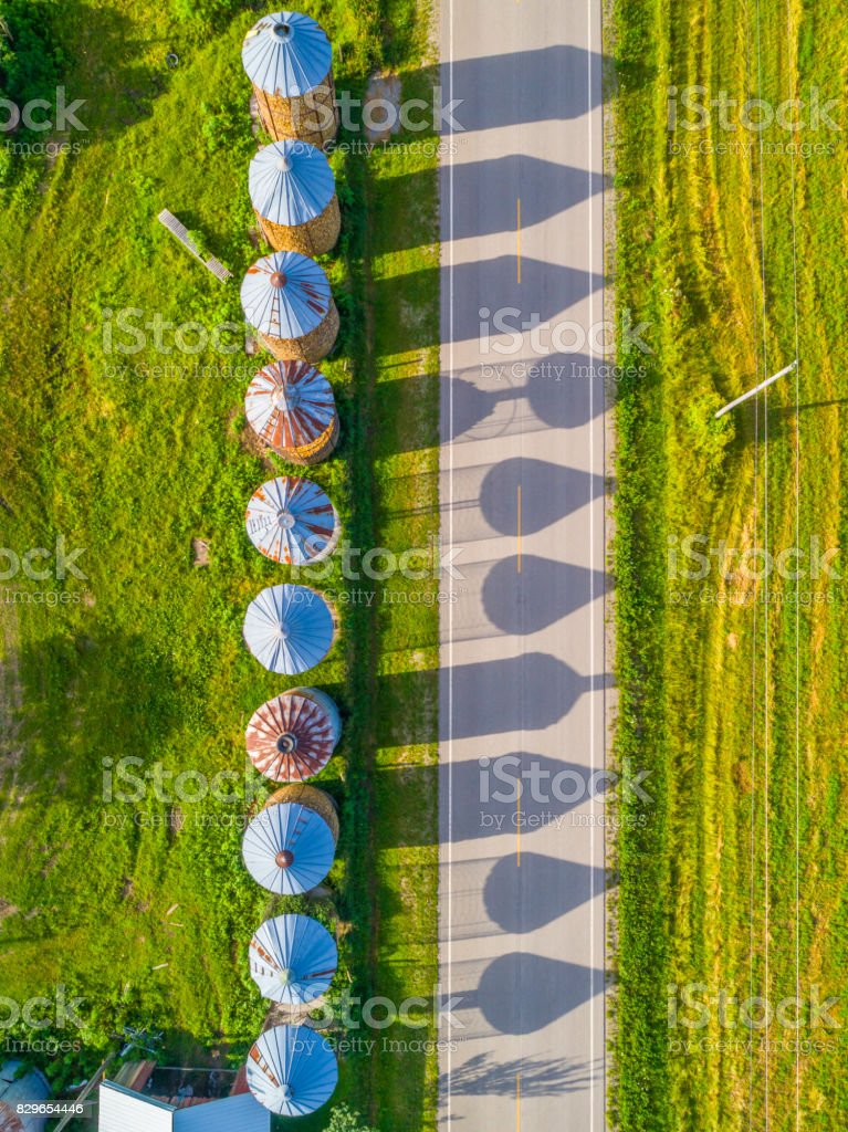 Corn cribs cast long shadows on country road, aerial view stock photo