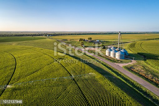 aerial view of corn field with sprinkler, silo, and farm buildings in eastern Colorado