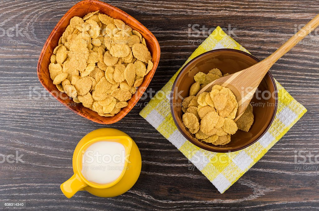 Corn flakes in bamboo bowl and jug milk on table stock photo