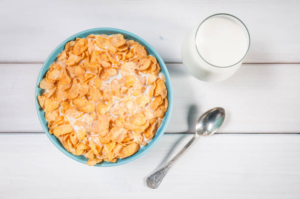 copos de maíz en un tazón azul - corn flakes fotografías e imágenes de stock