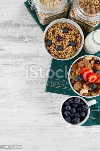 Corn flakes with nuts, berry fruit and dry cranberries on white wooden table background with copy space
