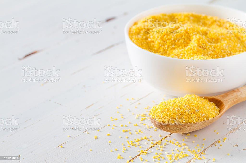 Corn grain in white bowl, wood spoon, white wood background stock photo