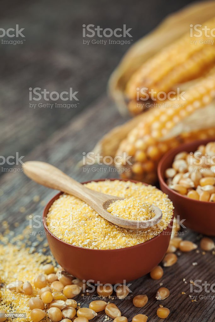 Corn groats and seeds in bowls, corncobs on background. stock photo