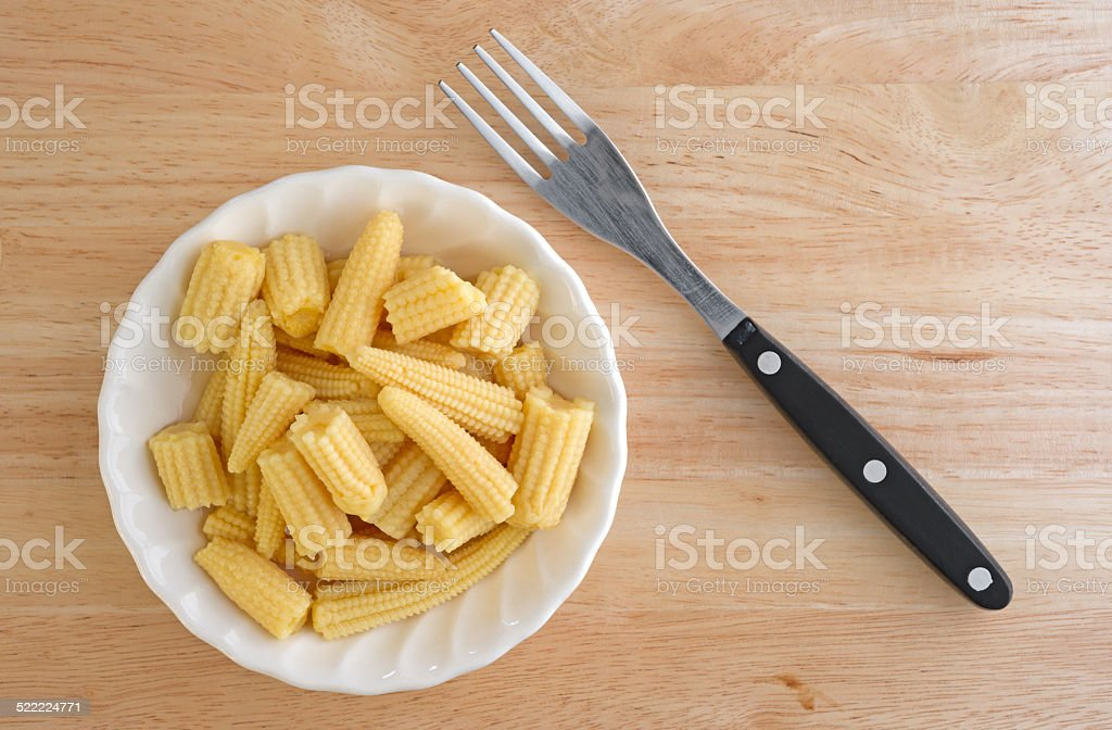 Corn nuggets in white bowl with fork stock photo