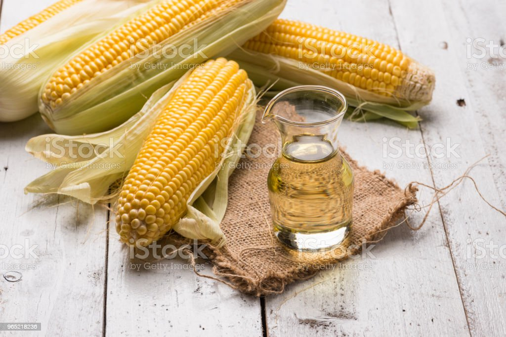 Corn oil and corn on rustic wood background royalty-free stock photo