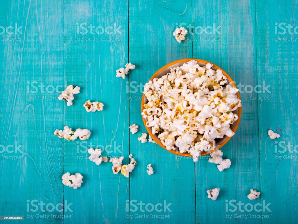 corn popcorn on a blue wooden background, as a snack for watching movies stock photo