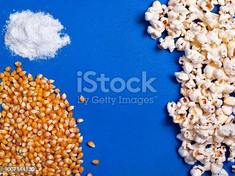 istock Corn seeds, salt, ready popcorn on blue background top view 1007144130