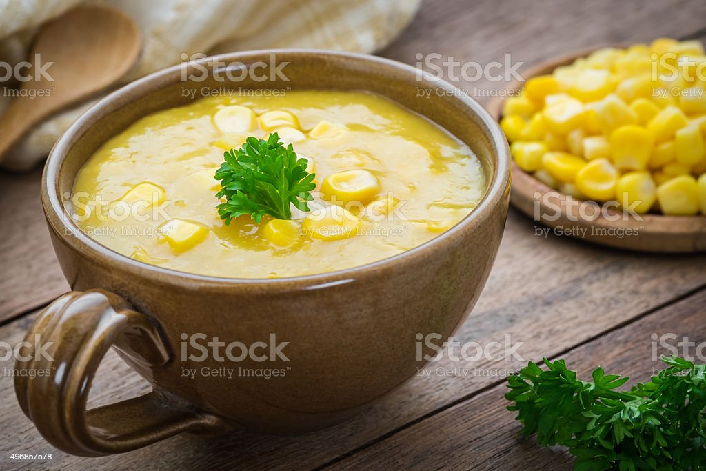 Corn soup in bowl and sweet corn on plate stock photo