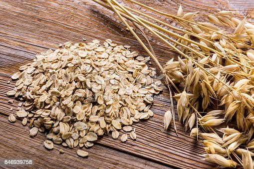 istock Corn spikes and oat flakes on a wooden background 846939758