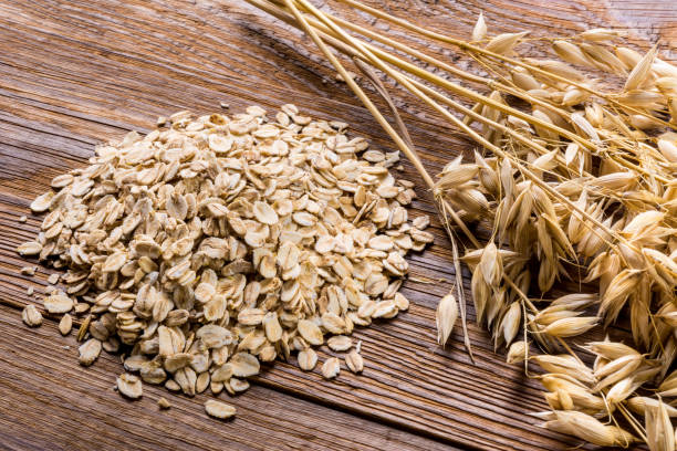 Corn spikes and oat flakes on a wooden background stock photo