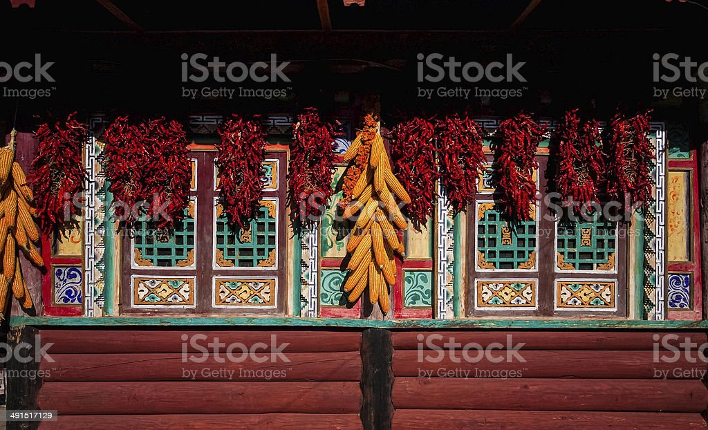 Corn-cobs and red peppers on window of Tibetan cottages, Sichuan. stock photo