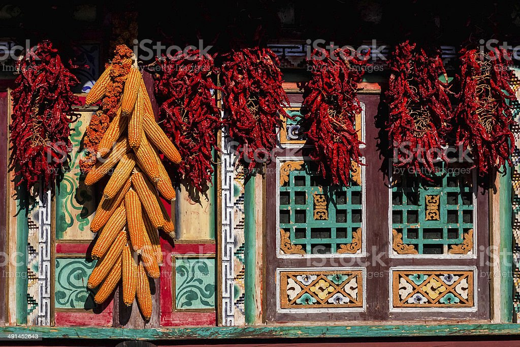 Corn-cobs and red peppers outside the Tibetan cottage , Sichuan, China. stock photo
