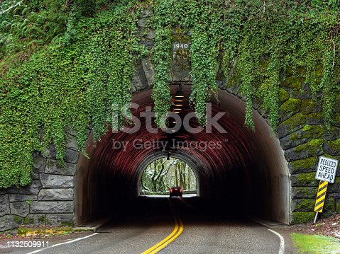 A view looking into Cornell Tunnel #1 on Cornell road in Portland, Oregon. Built in 1940 sign is visible at the top of the tunnel, surrounded by green vegetation. Red reflection from the tail lights of a car just about to leave the tunnel.