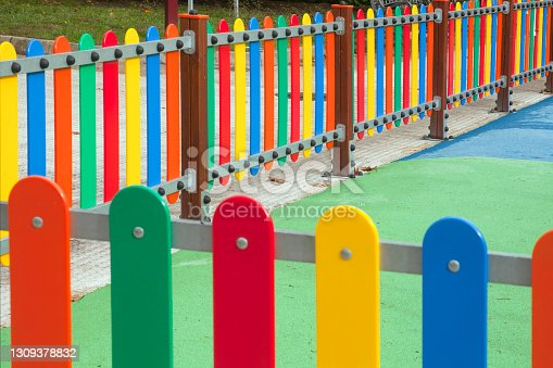 Corner and perspective of multicolored fence High angle view of multicolored fence surrounding a children playground, green soft flooring. Galicia, Spain.