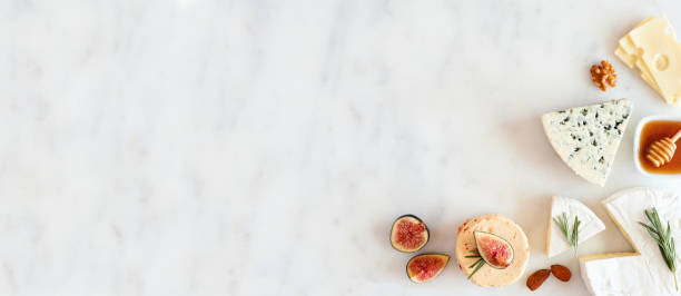 Corner border with a selection of cheeses, figs, nuts and honey on a white marble background with copy space stock photo