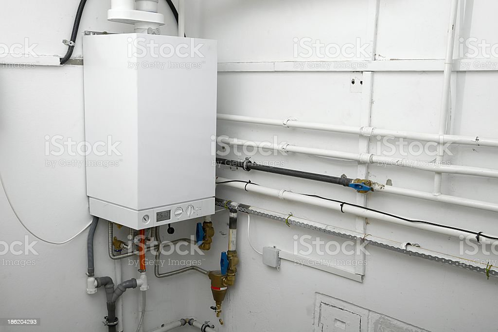 Corner of a room with white boiler and connectors stock photo