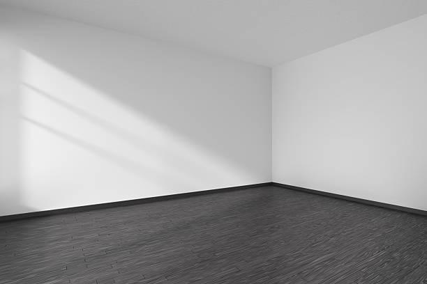Corner of empty white room with black parquet floor ストックフォト