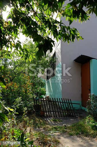 Corner of multi-colored house behind broken fence