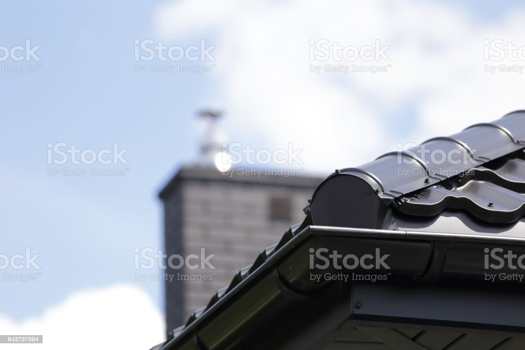 Corner of the new modern house with gutter roof and chimney. stock photo