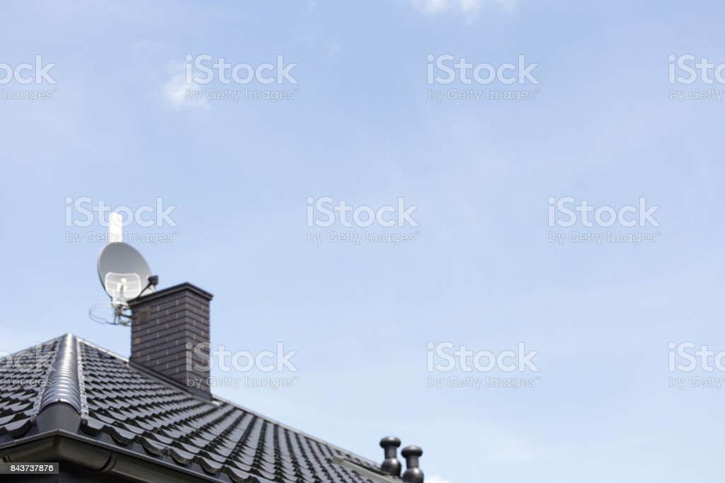 Corner of the new modern house with gutter roof, chimney and TV antenna. stock photo