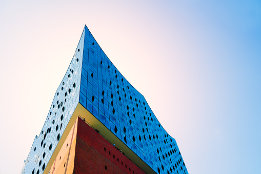 Corner or Edge of Elbphilharmonie. Wide angle - bright blue sky and sun light with flares over red brick building with blue windows facade, Hamburg, Germany