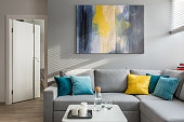 Living roon with corner sofa, colorful cushions and white coffee table