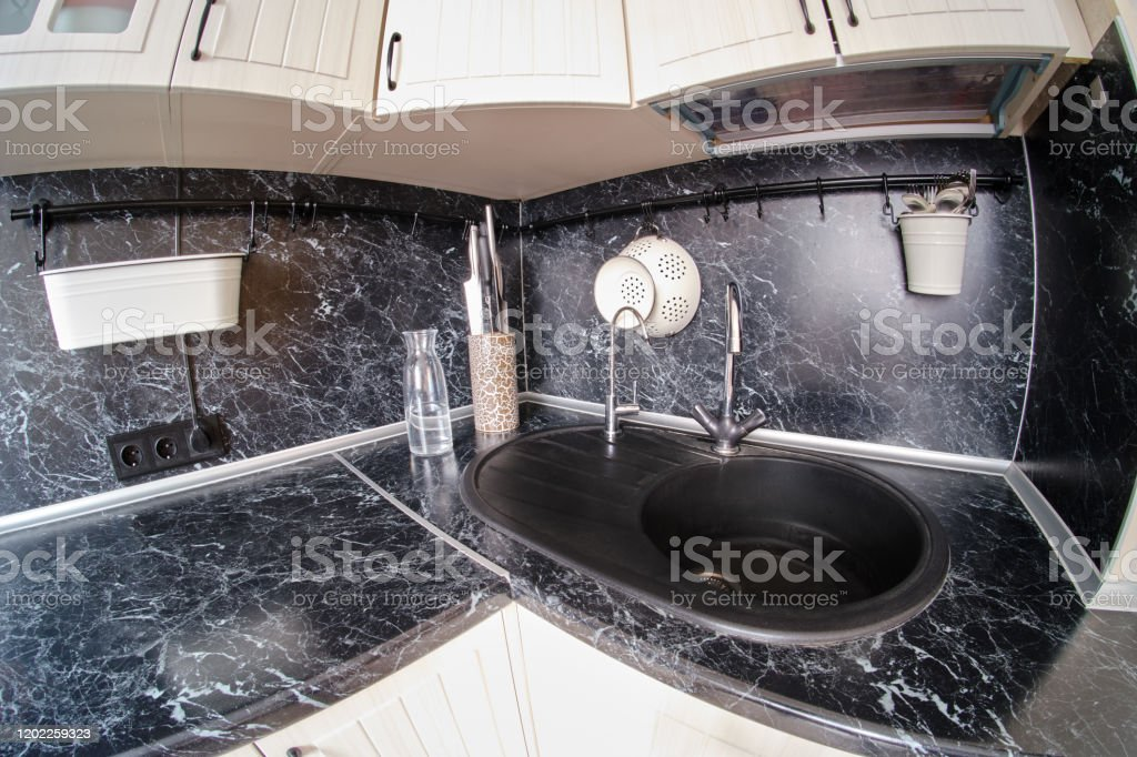 Corner With Sink In A White Kitchen With Black Marble Top With Railing Tv Knives Bottle And Cutlery Above The Table Stock Photo Download Image Now Istock