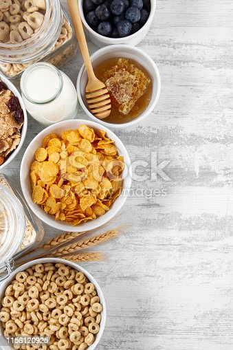 Cornflakes and breakfast cereals with fresh berries and honey on white wooden table