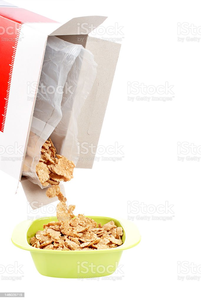 Cornflakes are poured from a box into a green bowl stock photo