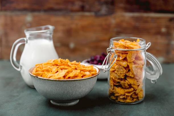 cereales copos de maíz y leche en un vaso. concepto de desayuno por la mañana - corn flakes fotografías e imágenes de stock