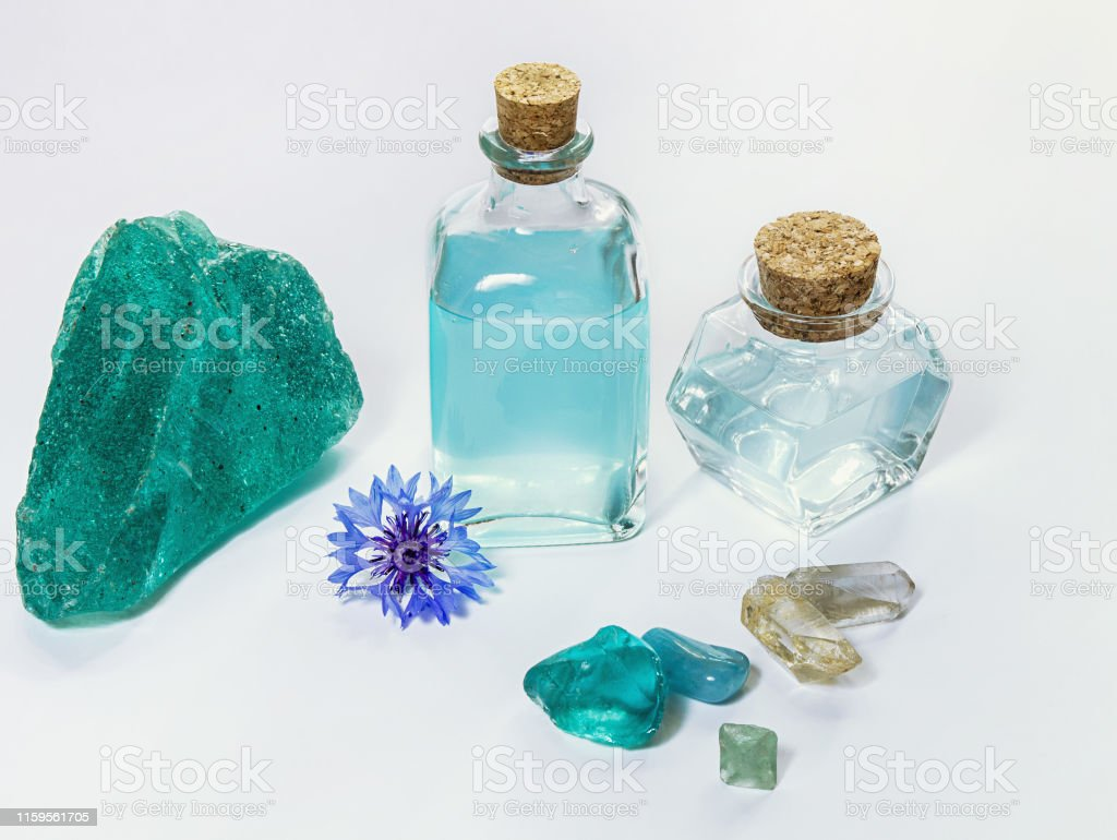 Cornflower flower and blue water or aromatherapy oil in glass bottle....