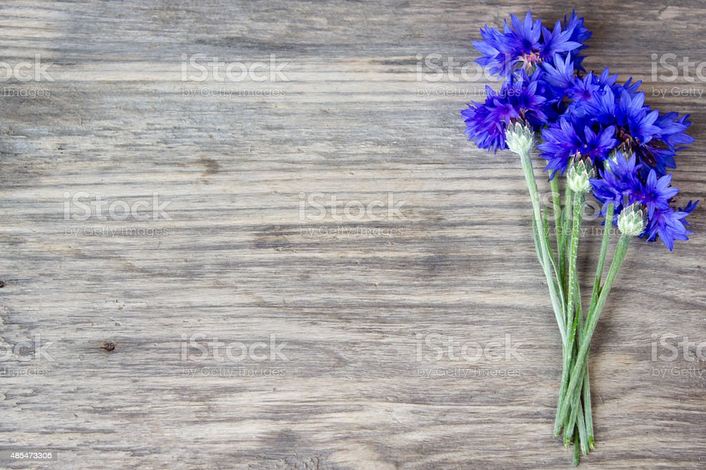 cornflowers on the old wooden table, rustic with copy space stock photo