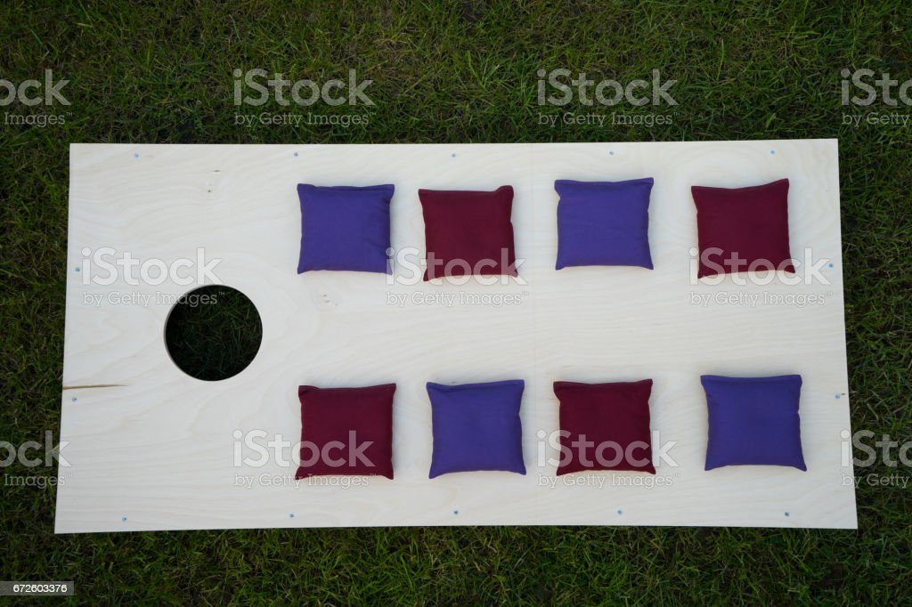 Cornhole Board Flat Lay with beanbags on grass stock photo