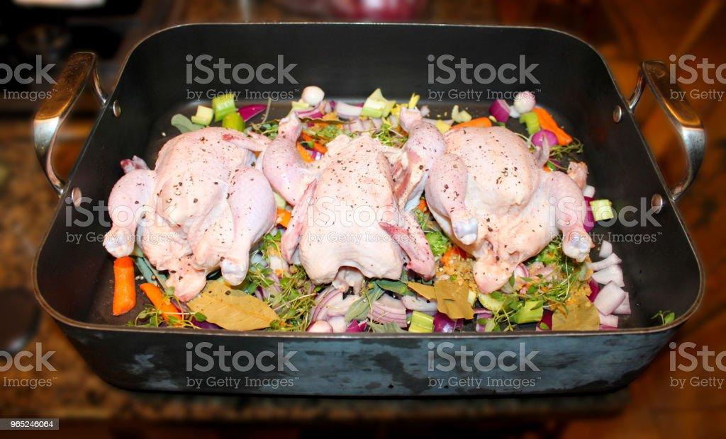 Cornish jogo galinhas em verduras em Roasting Pan pronto para cozinhar - foto de acervo
