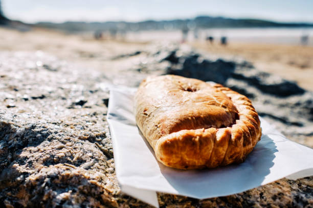 Cornish pasty on rocks overlooking Fistral Beach, Newquay, Cornwall on a bright sunny Autumn day. stock photo