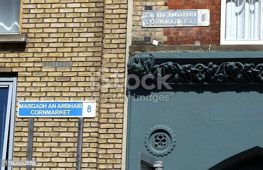 An old and new Cornmarket street sign in English and Irish language in the Liberties area of Dublin city centre.