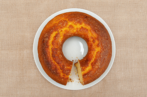 Cornmeal cake (Bolo de Fuba) cut Brazilian style on a white plate. Isolated on jute. Top view. Horizontal shot