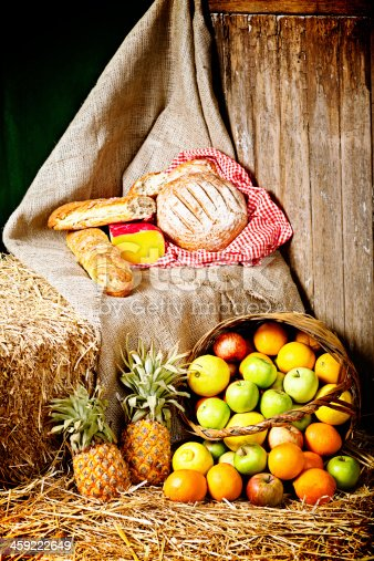 Fresh rustic bread, golden cheese, and a basket full of ripe fruit all rady for a delicious picnic lunch.